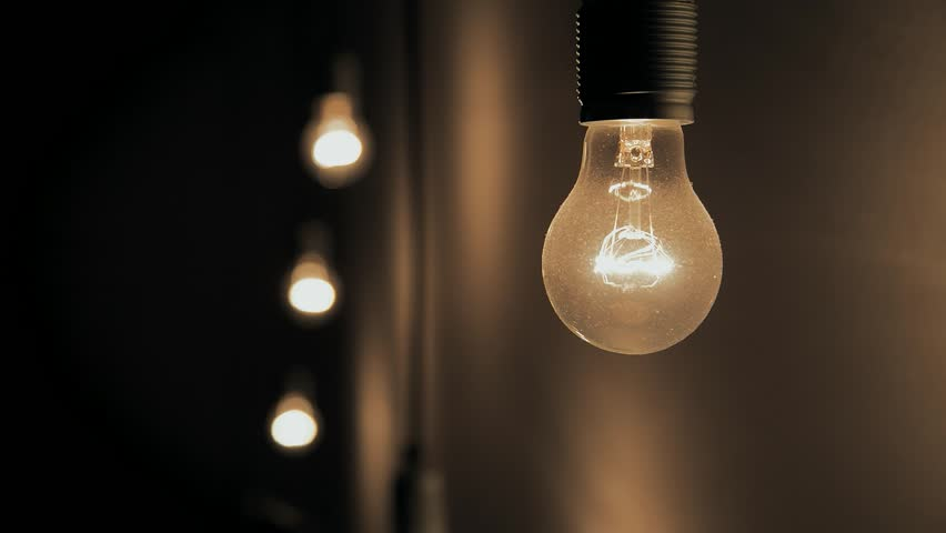 a hanging dimmed light bulb 3 bulbs in the background warm mood