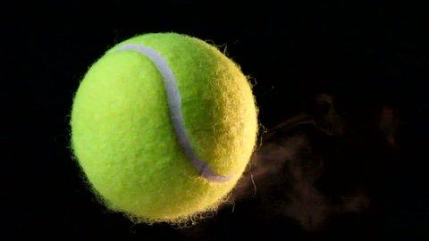 Tennis ball spins through the air, emits a trail of smoke. Tennis concept. 1080p