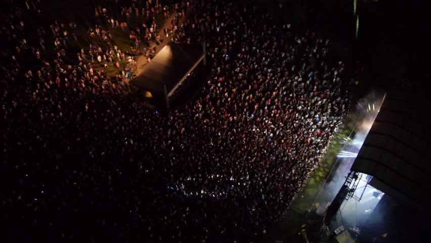 AERIAL: Crowd of people dancing on a music festival