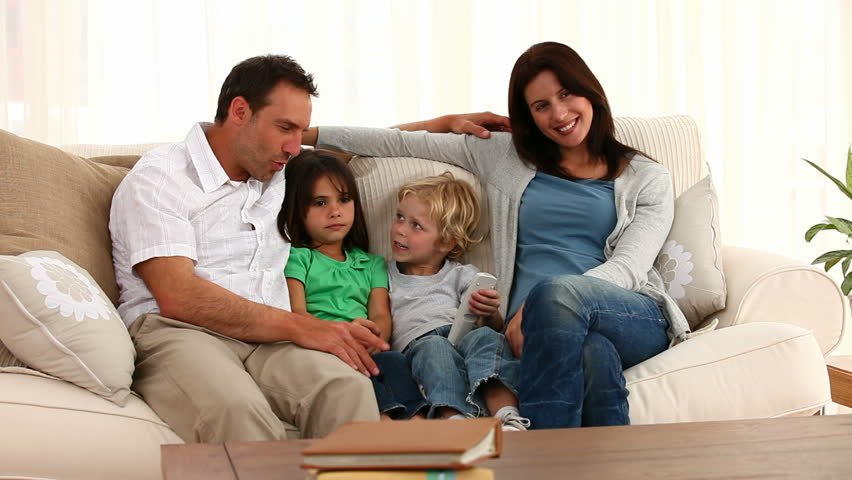 Cute Family Posing In Front Of The Camera Sitting On The Sofa At Home   HD
