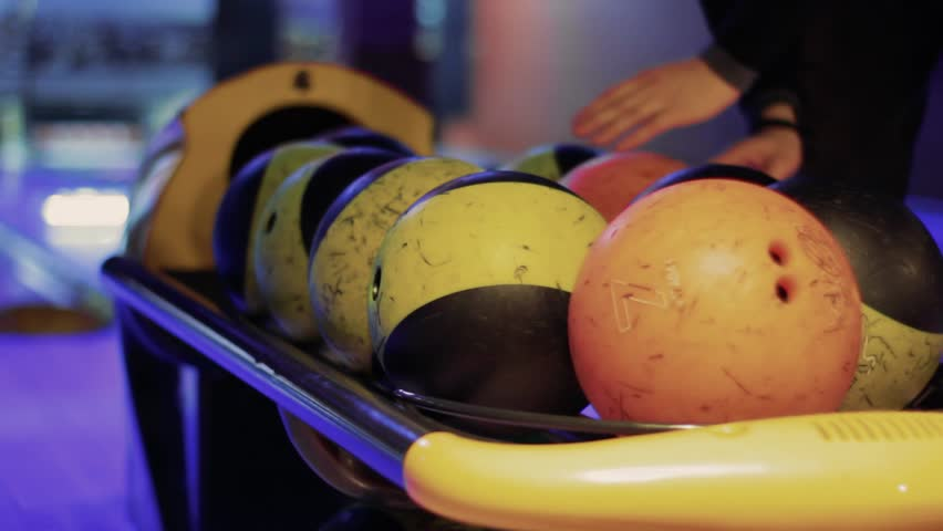 Person takes Bowling balls with bowling alley in background. Group game. Bowling strike competition