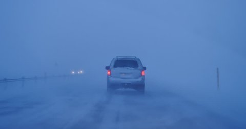 Low visibility driving, traffic headlights in blowing snow during high winds blizzard 4k.mov