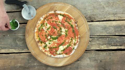 Caprese pizza top view. Tomatoes, pesto sauce and basil.