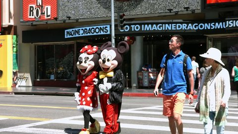 LOS ANGELES, CALIFORNIA, USA - APRIL 30, 2015: Mickey Mouse and Toddler Minnie mouse on Hollywood Boulevard in Los Angeles, California, 4K
