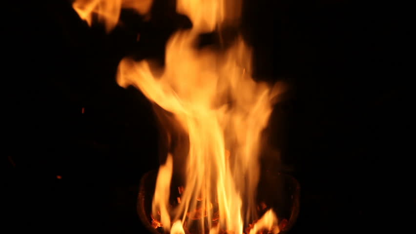 The flame of a stove burns in the crucible. The fire flares up and takes different colors depending on the fuel burned.