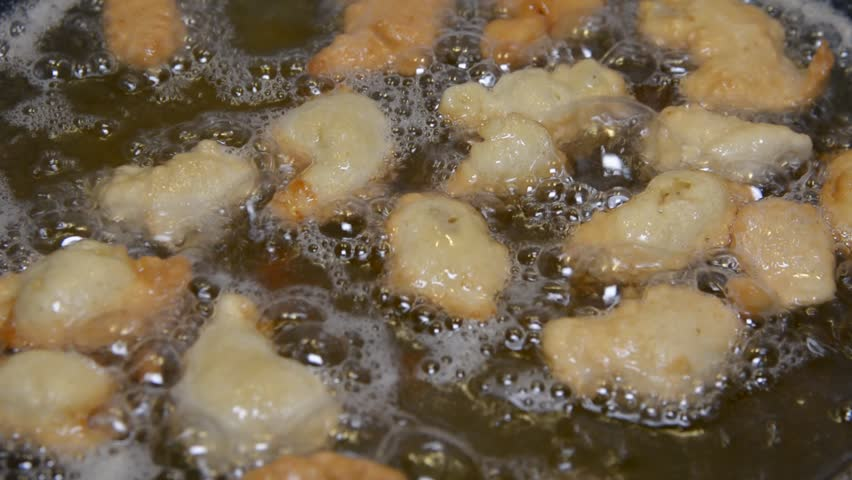 Hot cooking oil in a frying pan with chicken nuggets