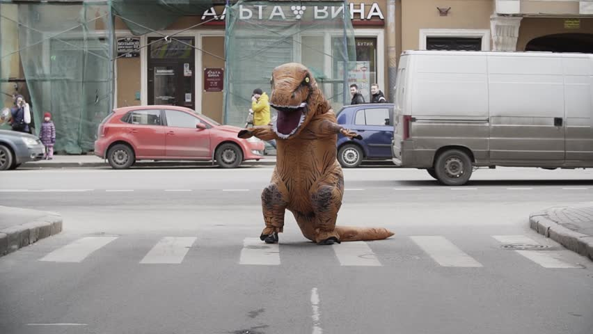 SAINT PETERSBURG, RUSSIA - APRIL 1, 2017: Man in dino mascot jumping and dancing at city street crosswalk with lots of cars. Sunny day. Slow motion