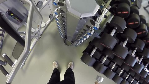Man (first person view) stand, raise and lower dumb-bells in right hand in fitness club.