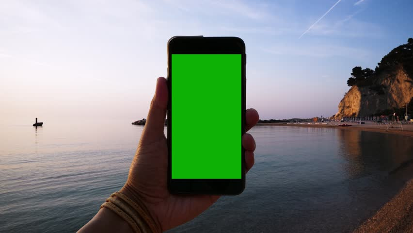 Close up of hand holding a smartphone with green screen display before a lonely beach at sunrise | Shutterstock HD Video #1006704511