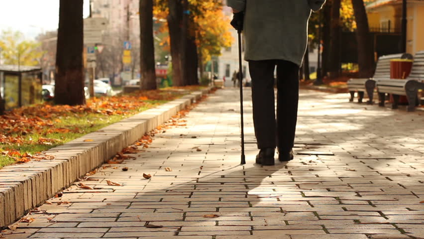 Lonely, old, person walking down street with stick, limping. Gait, legs disease