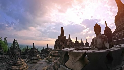 Scenic panoramic view of Borobudur temple at sunrise with beautiful sky and Buddha stone sculpture in meditation pose sitting in buddhist stupa. Traveling to Java Indonesia