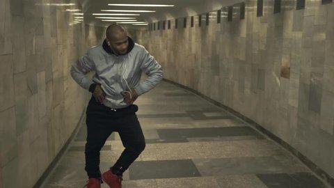 Black man dancing hip-hop in an underground crossing