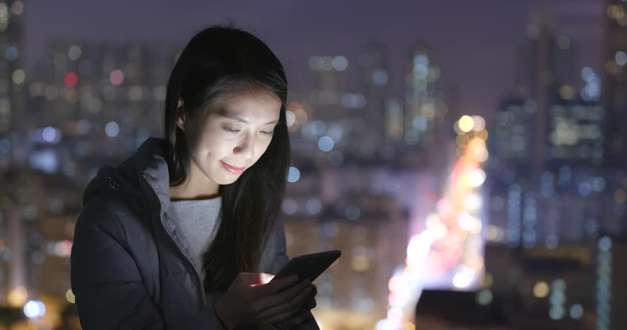 Woman use of cellphone over city background at night | Shutterstock HD Video #1006722061