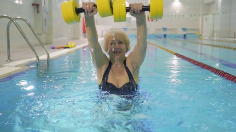 Senior woman train her hands with dumbbells in the swimming pool