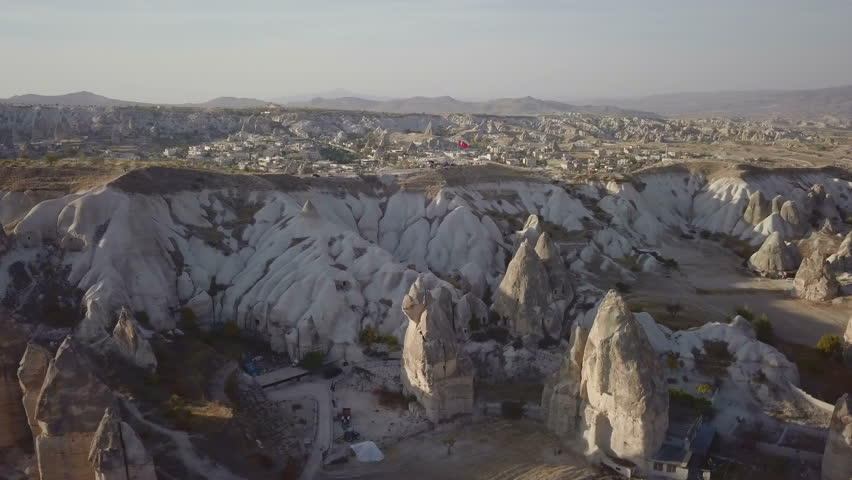 High key advancing aerial forward turning dynamic view of Cappadocia fairy chimney landscape over ridge with Goreme town and Uchisar Castle background in Kapadokya, Turkey. 4k