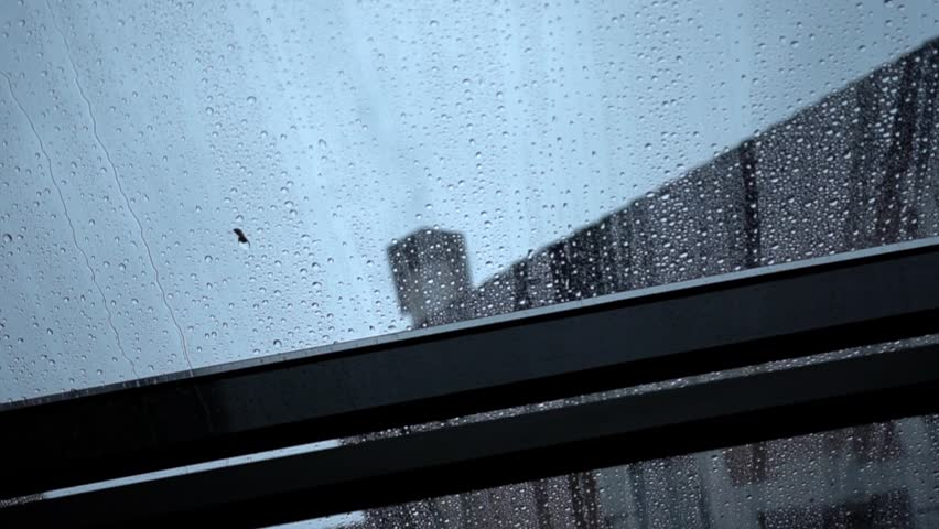Rain drops slowly flow down the transparent roof window leaving water traces, close-up. A view through flat roof light on a dark building and grey sky background. Gloomy rainy day.