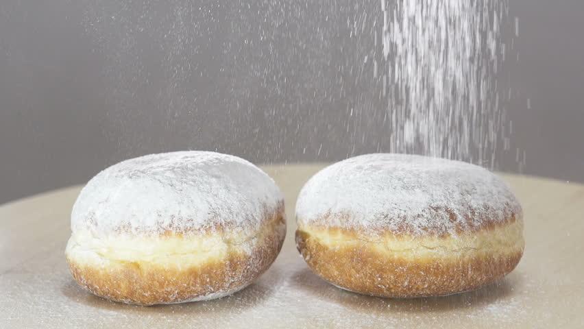 Spreading Sugar Powder On Hanukkah Doughnuts . Slow motion #1006784071