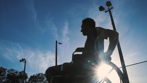 Silhouette of disabled athlete in wheelchair playing tennis outdoors