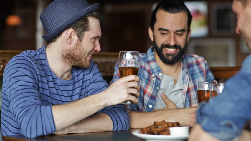 People, leisure, friendship and celebration concept - happy male friends drinking beer, eating bread snack and clinking glasses at bar or pub | Shutterstock HD Video #10067861