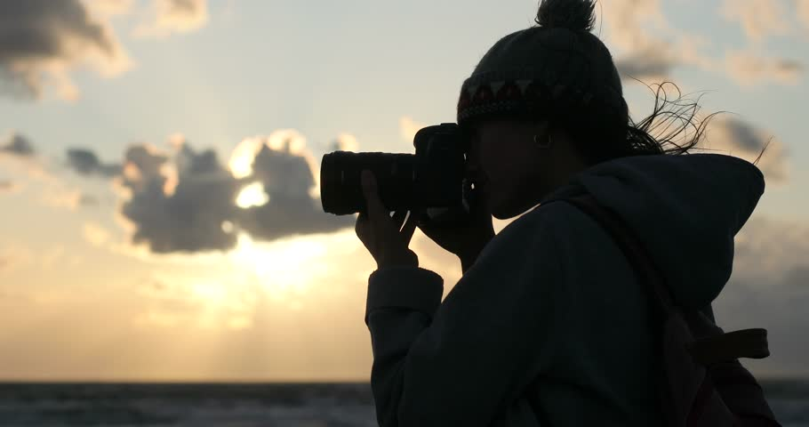 4k Young woman photographing sunset sea sky wind evening close up. Female silhouette takes pictures holding professional long lens camera focusing waiting for moment. Camera equipment in bad weather