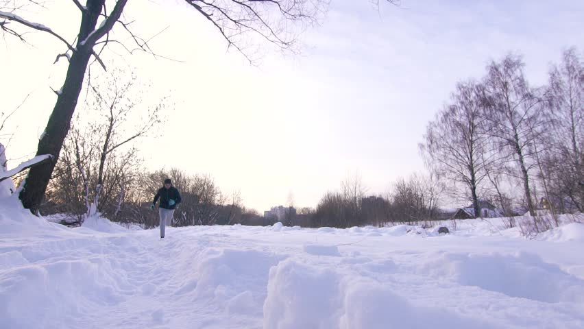 Man at sunset jogs in the winter on deep snow in the park slow mo | Shutterstock HD Video #1006808971