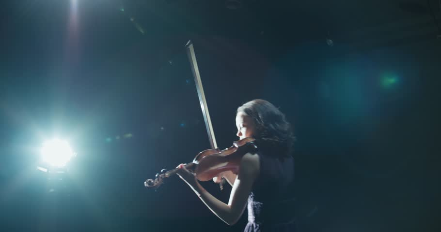 beautiful young girl playing the violin during the concert