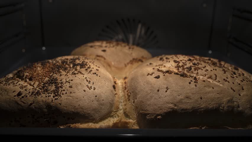 Time-lapse of rising and baking a Rustic home-made breads with sunflower and sesame seeds in baking pan in the oven