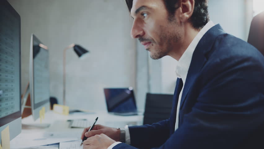 Businessman working at sunny office on desktop computer while sitting at the table.Blurred background. | Shutterstock HD Video #1006858711