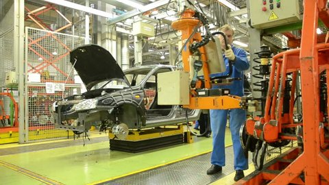 TOGLIATTI - SEP 30: Workers install the absorber on the car Lada Kalina of factory AutoVAZ, on September 30, 2011 in Togliatti, Russia.