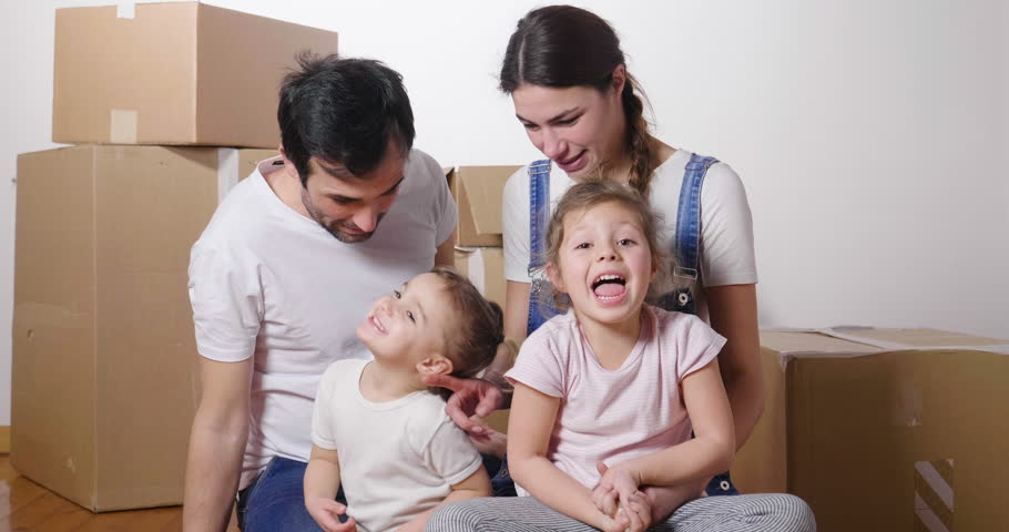 Portrait of a beautiful happy and smiling family holding the house shaped meter just arrived in the new house to start a new path together. Concept of: love, family, home. | Shutterstock HD Video #1006877881