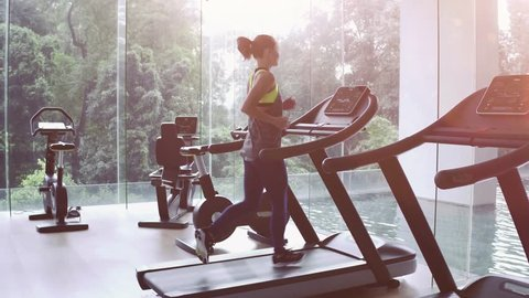 SLOW MOTION. Cute Asian girl on treadmill at gym. Panoramic window, healthy fitness lifestyle concept