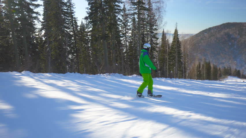 Sportsman in bright green clothes jumps on board upon a slope of the hill at sunny winter day | Shutterstock HD Video #1006903081