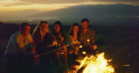 Group of friends relaxing around campfire roasting marshmallows, sunset bonfire lifestyle