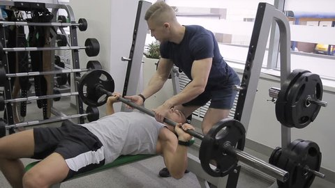 Young athlete is doing bench press with help of trainer in gym. Man raises free weight under control of instructor in sports club. Handsome guy lies on bench and does exercise with iron object
