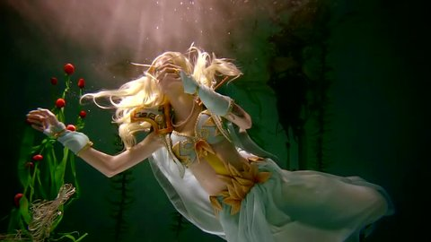 Engaging woman in elf costume is posing underwater with many flowers. She is reaching tulips with her hand. Reflection on the surface.