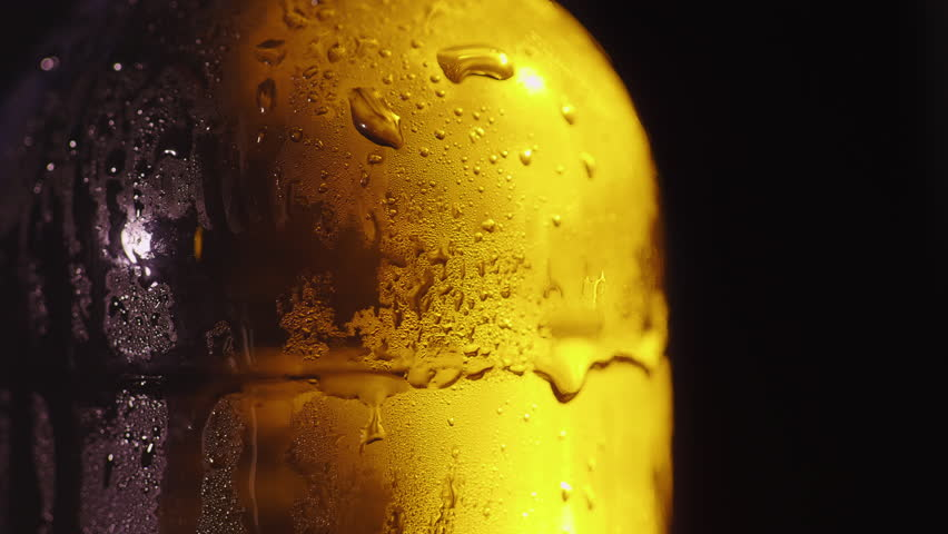 Close-up of a glass bottle with drops of condensed water. Cold drink concept. On a black background | Shutterstock HD Video #1006969771
