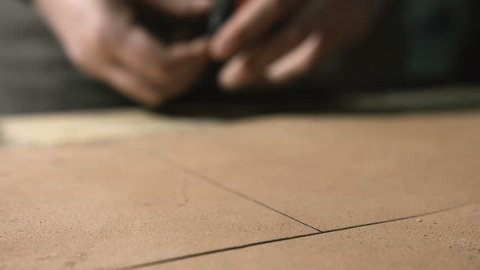 Leather craftsman making an handmade genuine leather bag. Close up of his hands taking measures using a tape measure 1