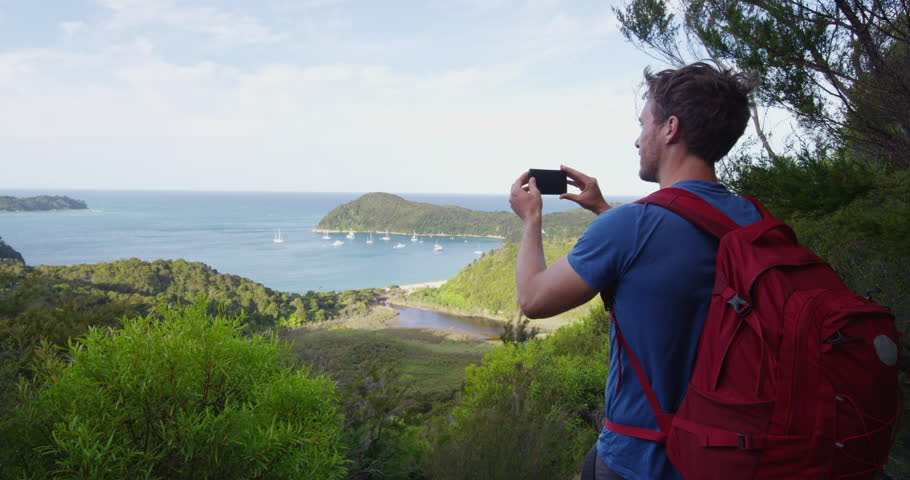 New Zealand travel man taking pictures with smart phone of the Anchorage in Abel Tasman National park, New Zealand vacation. Male backpacker tramping hiking on Abel Tasman Coast Track. SLOW MOTION.