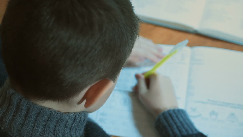 Boy in warm sweater writes with pen in his notebook and flips textbook page | Shutterstock HD Video #1007007631