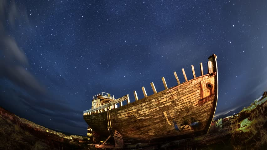 Old wrecked wooden traditional fishing boat at night moving stars sky background -  4K timelapse