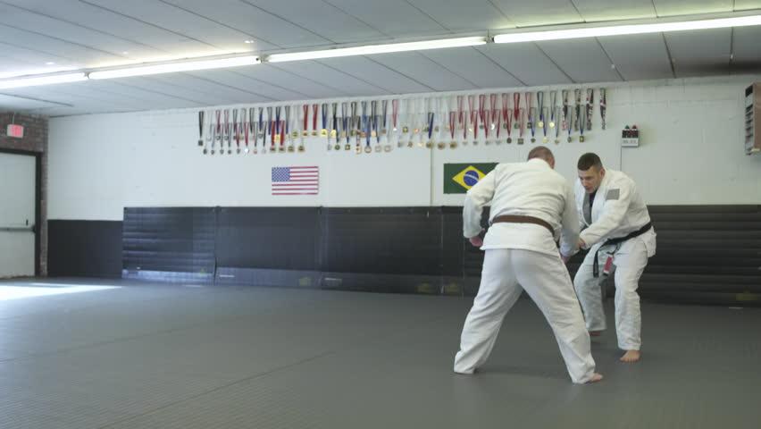 Mid adult men practicing Jiu-jitsu moves