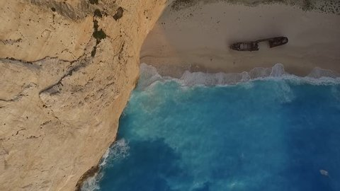 Aerial view of Navagio Shipwreck Beach in Zakynthos Greece sliding with the drone upon the boat while waves are crashing at sunset amazing colors