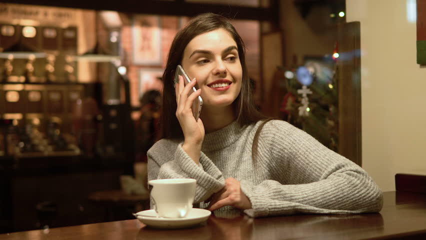 Beautiful slim brunette having coffee while talking on the phone, indoor shot during holiday season