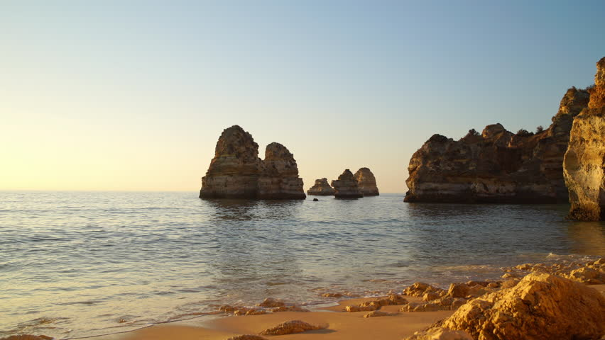 Waves breaking on sandy ocean beach Praia da Balanca with famous beautiful coastal cliffs in Lagos, Algarve, Portugal