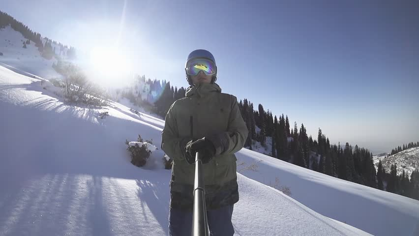 Snowboarder adventure to the big mountain. Snowboarder man making selfie use action camera gopro #1007068561