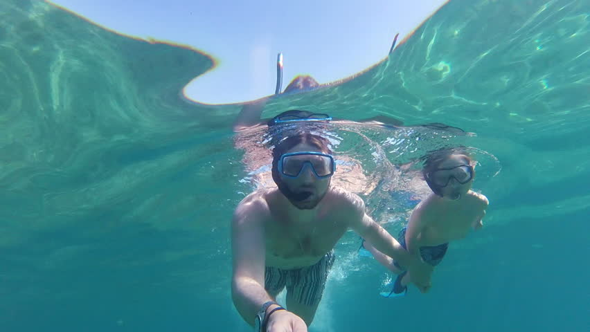 Father and son with flippers, mask, snorkel and a selfie stick swimming in the sea, gopro underwater footage | Shutterstock HD Video #1007069731