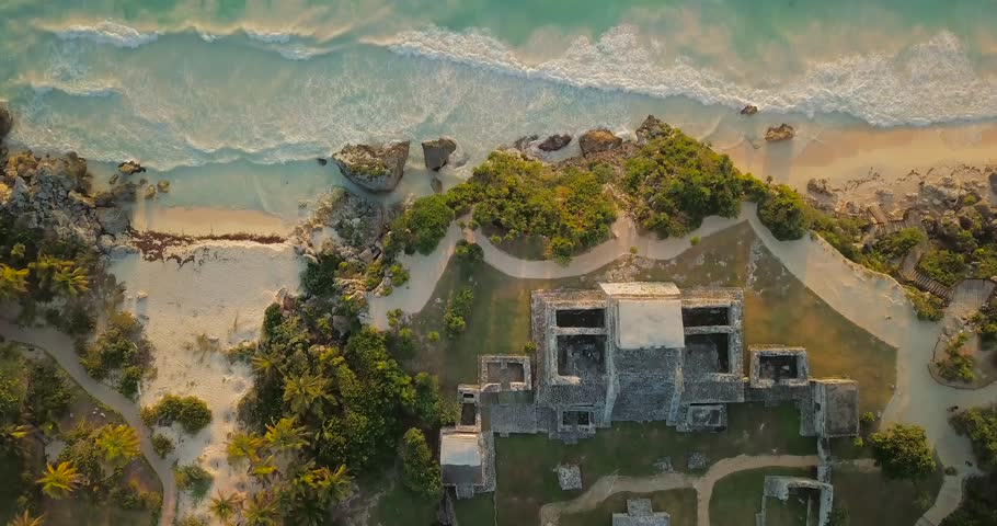 Birdseye view from above Mayan temple Ruin drone sky shot over sea with waves in Tulum Mexico at sunrise