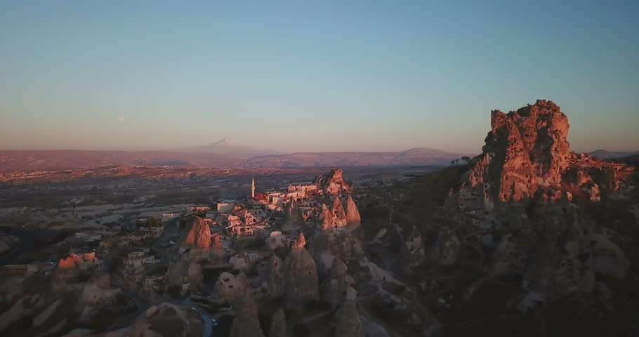 High angle aerial drone point of interest orbit view clockwise around Uchisar Castle and otherworldly fairy chimney landscape valley in evening at Cappadocia, Turkey. 4K at 23.97fps