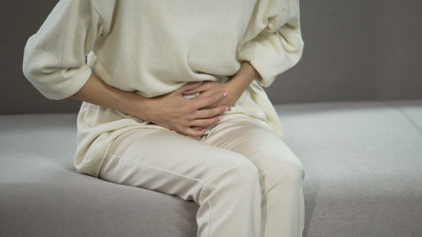 Young woman suffering from strong menstrual or stomach ache, gynecology problems