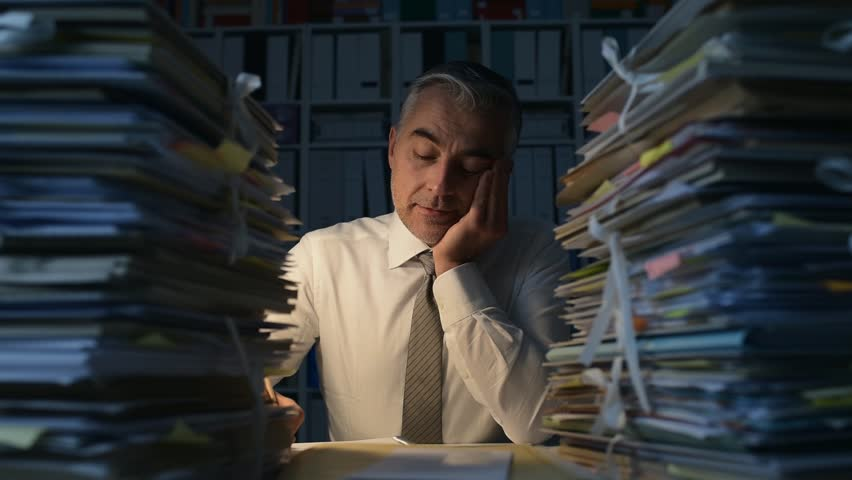 Tired businessman working late at night, he is overwhelmed by work and his desk is filled with paperwork, work overtime and deadlines concept | Shutterstock HD Video #1007116471